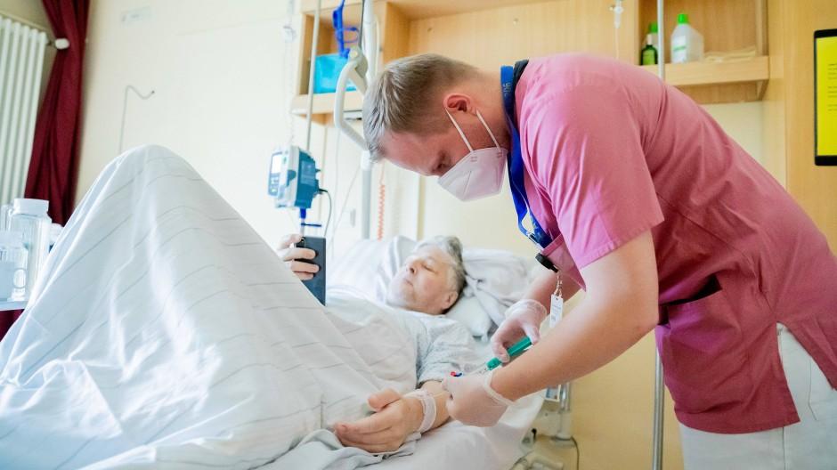 Pfleger mit einem Patienten in einem Berliner Krankenhaus