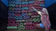 Eine indische Arbeiterin zählt die Ladung Kunststoffseile auf einem Lastwagen nach.