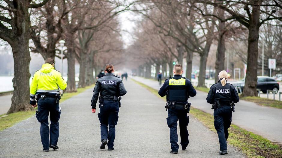 Einsatzkräfte der Polizei gehen am Maschseeufer in Hannover entlang, um die Einhaltung der Maskenpflicht zu kontrollieren.