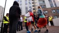 """Bewohner verlassen ein Hochhaus in der Siedlung """"Chalcots Estate"""" in London."""