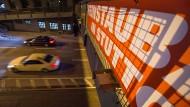 Autos fahren an einem Feinstaub-Plakat in Stuttgart in der Nacht vorbei.