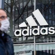 Ein Mann in Schutzmaske steht vor einer Adidas-Filiale in Berlin. Der Sporthersteller will in der Krise keine Miete zahlen – und sorgt damit für Aufregung.