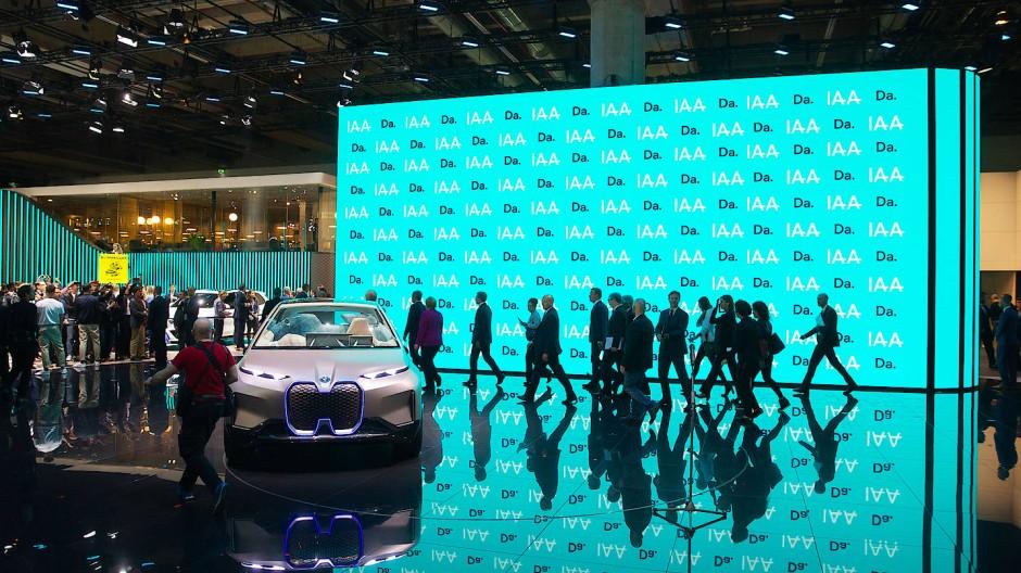 Alle hinter Merkel her: Nach der Eröffnung der IAA verlässt die Kanzlerin den Messestand von BMW.