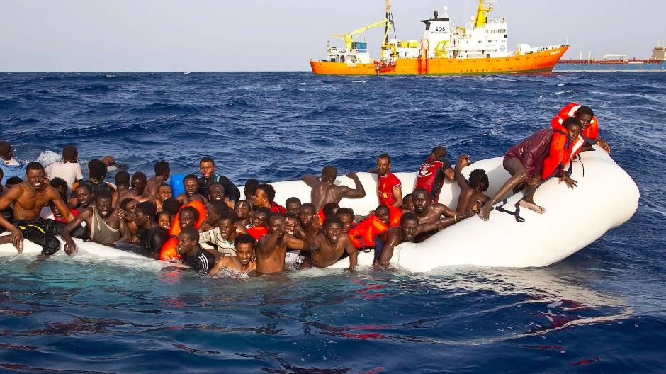 Flüchtlinge sitzen auf dem Mittelmeer in einem sinkenden Schlauchboot. Die EU will gegen Schleuser vorgehen.