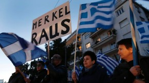 Supporters of the extreme-right Golden Dawn party hold Greek flags during a rally outside the German emapassy in Athens