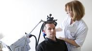 Erste Verfahren wirken gezielt auf Hirnregionen, die für das Schmerzgeschehen entscheidend sind: Transkranielle Magnetstimulation in einer Klinik in Frankreich.