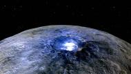 Der Occator-Krate, aufgenommen von der Raumsonde Dawn aus einer Höhe von 4425 Kilometern. Darstellung in Falschfarben, die  die Unterschiede in der Oberflächenzusammensetzung hervorheben. Rot entspricht dem Wellenlängenbereich um 0,97 Mikrometer (nahes Infrarot), Grün dem Wellenlängenbereich um 0,75 Mikrometer (rotes, sichtbares Licht) und Blau dem Wellenlängenbereich um 0,44 Mikrometer (blaues, sichtbares Licht).