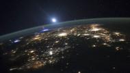 Ein Koboldblitz erscheint links unterhalb des aufgehenden Mondes.