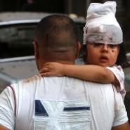 Ein von der Explosion verletztes Kind wird von einem Mann durch die Innenstadt von Beirut getragen.