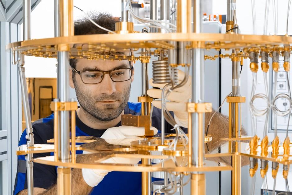 Ein Forscher hantiert an dem  Kryostaten für den Quantencomputer OpenSuperQ.