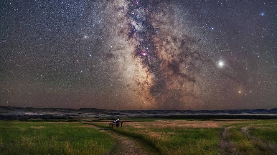 Auf dem Boden der Tatsachen staunt es sich immer noch am großartigsten: Die Astrophysik spekuliert von erstaunlichen Fundamenten aus. Ungetrübter Blick auf das Zentrum der Milchstraße im Nationalpark Grasslands in der kanadischen Provinz Saskatchewan.