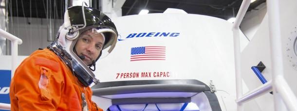 """Bitte einsteigen! Ein """"Astronaut"""" öffnet die Luke einer CST-100 Kapsel von Boeing."""
