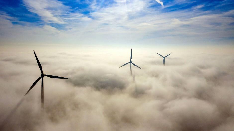 Windkraftanlagen ragen in der Nähe von Alpen-Veen in Nordrhein-Westfalen aus dem Morgennebel.
