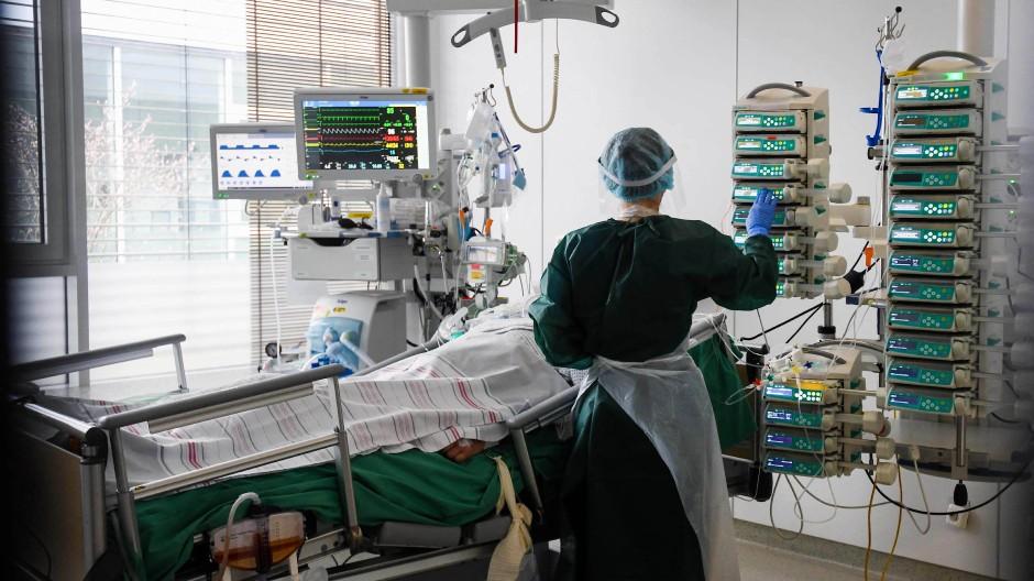 Eine Pflegerin kümmert sich um einen COVID-19-Patienten auf der Intensivstation im Universitätsklinikum in Essen.