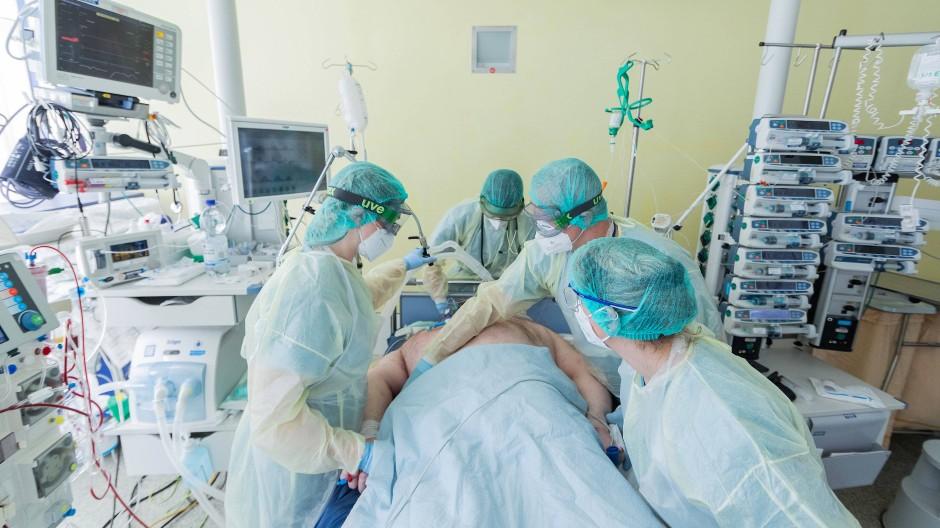 Vier Pflegekräfte sorgen sich um einen schwerstkranken Corona-Patienten auf einer Intensivstation im Universitätsklinikum Bonn.