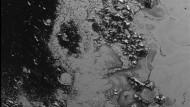 """Bis zu eineinhalb Kilometer hoch sind Plutos Eisberge in der """"Norgay Region"""", im Westen der """"Tombaugh Region"""". Die dunkle Fläche besteht aus gefrorenem Kohlendioxid. Dort sind auch Einschlagskrater zu erkennen. Die Aufnahme stammt vom 14. Juli, als New Horizons noch 77.000 Kilometer vom Zwergplaneten entfernt war."""