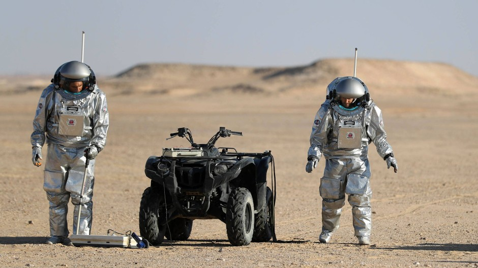 Zwei Raumfahrer erkunden die Beschaffenheit des Marsbodens in der Dhofar-Wüste im Oman.