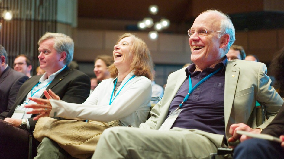 David J. Gross (rechts), seine Frau Jacquelyn Savani und der australische Astrophysiker Brian Schmidt während der Übertragung der Cern-Pressekonferenz anlässlich der Entdeckung des Higgs-Teilchen in der Inselhalle in Lindau am Bodensee, am 4.Juli.2012.