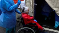 """Was passiert da drin? Eine alte Dame wird am 9. April 2020 in Lissabon in ein als """"Triage Area"""" ausgewiesenes Zelt gebracht."""