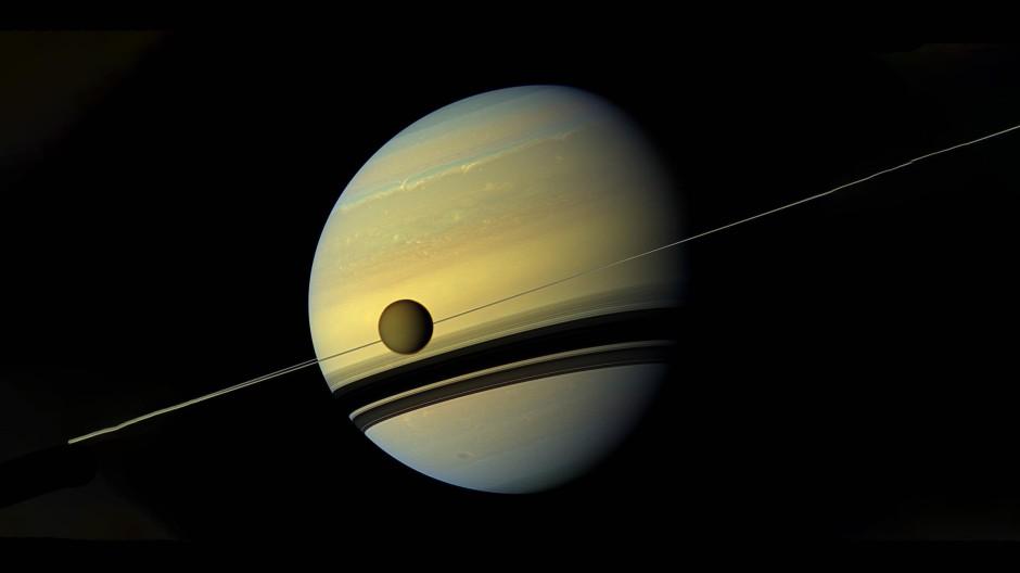 Der Herr der Ringe und sein größter Mond, der Titan, fotografiert von der Cassini-Sonde. Die Ringe, als dünnen Streifen zu erkennen, werfen ihre Schatten auf die Oberfläche des Gasplaneten.