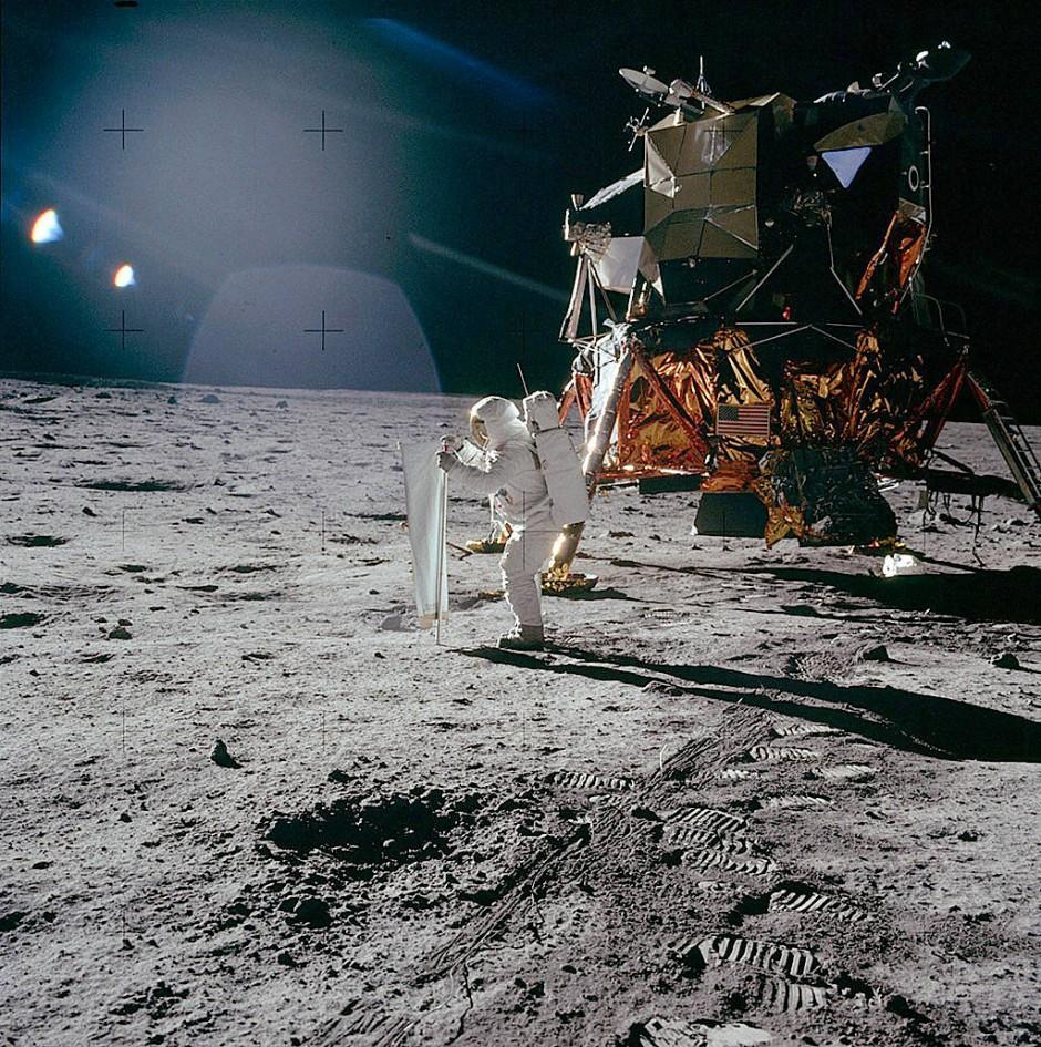 """Buzz Aldrin entfaltet (noch vor der amerikanischen Flagge) auf der Mondoberfläche das """"Solar Wind Composition Experiment"""": ein rund 1,40 Meter hohes Sonnenwindsegel, entwickelt von Physikern an der Universität Bern."""
