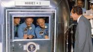 Zurück auf der Erde: Neil Armstrong, Michael Collins und Edwin Aldrin im Bergungsschiff U.S.S. Hornet im Gespräch mit Präsident Nixon (von links nach rechts)