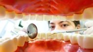 Zahnarzthelferin hinter einem künstlichen, überdimensionierten Gebiss.