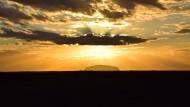 Bei dieser Beleuchtung unbedenklich als Fotomotiv: Uluru alias Ayers Rock kurz nach Sonnenaufgang von Westen - und aus 30 Kilometern Entfernung.
