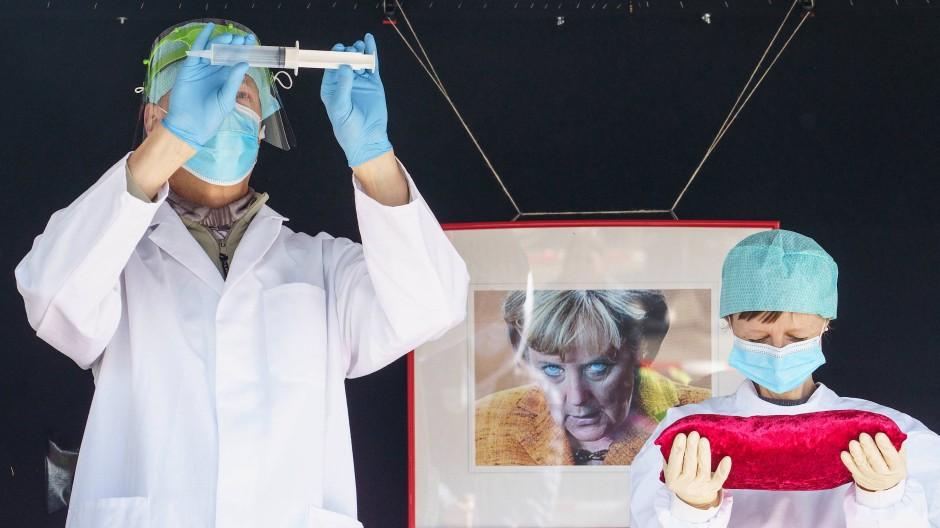 """Als """"heilige"""" Handlung kritisieren auf der Bühne Teilnehmer einer Kundgebung der """"Querdenken""""-Initiative in Darmstadt das Impfen gegen Covid-19."""