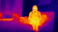 Mit Atemschutz-Maske hinter der Wärmebildkamera.