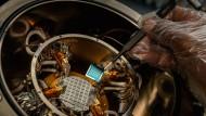 Mit einer Pinzette holen Forscher die Hochtemperatur-Transistoren aus ihrem Ofen. Die Schalter bestehen aus einem robusten organischen Halbleiter.