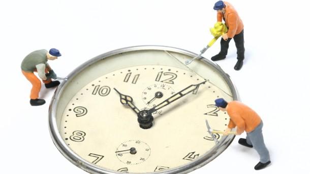 Arbeitszeitkonto - Fotoillustration aus Wecker und Bauarbeiter Preiser Figur