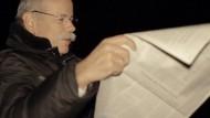 """Strahlende Sterne erleuchten den klaren Himmel über Stuttgart. Auf freiem Feld sitzt Dieter Zetsche in der nächtlichen Ruhe hinter einer  aufgeschlagenen Ausgabe der Frankfurter Allgemeinen Zeitung. Für das aktuelle Motiv der """"Kluge Köpfe""""-Kampagne hat sich der Daimler-Vorstandsvorsitzende unter dem Sternenhimmel fotografieren lassen – natürlich vor dem Großen Wagen."""