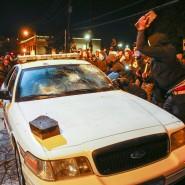 Demonstranten beschädigen in Ferguson einen Wagen der Polizei.