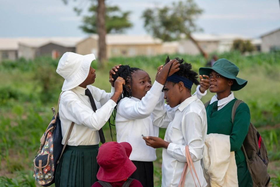 Fein sein, wenn der Unterricht beginnt. Junge Mädchen in Schuluniform kümmern sich um ihre Haare.