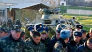 Gefangene? Ukrainische Soldaten werden auf der Militärbasis Belbek von mutmaßlich russischen Truppen mit einem Schützenpanzer bewacht.