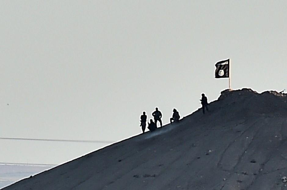"""Mutmaßliche Kämpfer des """"Islamischen Staats"""" neben einer IS-Fahne, die auf einem Hügel in der syrischen Stadt Kobane weht."""