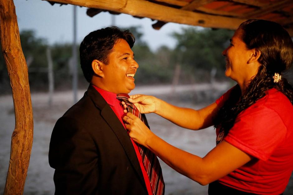 Claudia Adriana richtet die Krawatte ihres Ehemanns Crenilton Ferreira, bevor er den Gottesdienst  in der Deus Cristo para Todos Kirche in Palmeira Dos Reis eröffnet.