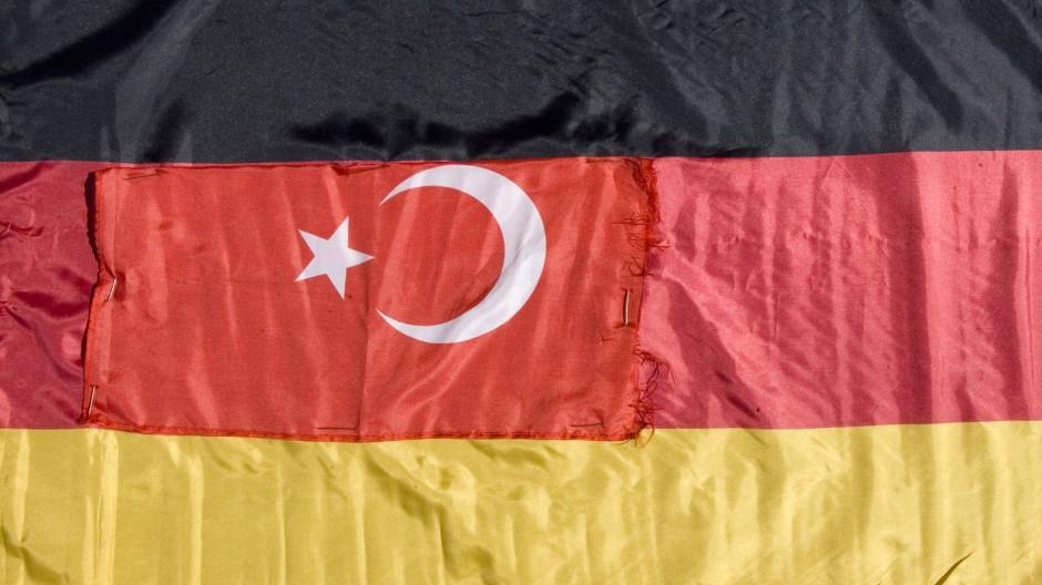 Deutsch, türkisch, oder beides? Eine Deutschlandfahne mit Halbmond und Stern, aus einem türkischen Imbiss in Deutschland.
